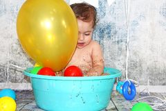 Cute adorable baby taking bath in blue tub stock photography