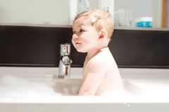 Cute adorable baby taking bath in washing sink and playing with water and foam. Cute adorable baby taking bath in washing sink and grab water tap. Little healthy Stock Images