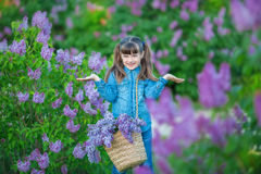 Cute adorable beautifull lady woman girl with brunette hair on a meadow of lilac purple bush.People in jeans wear. stock image