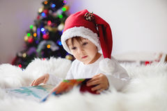 Cute adorable boy reading a book in front of the christmas tree Stock Image