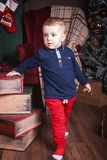 Small boy standing near books at christmas time royalty free stock photography