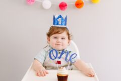 Cute adorable Caucasian baby boy in blue crown celebrating first birthday at home. Child kid toddler sitting in high chair eating