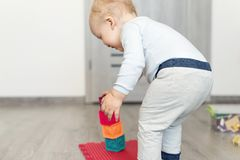 Cute adorable caucasian baby boy playing colorful toys at home. Happy child having fun building tower of soft rubber cubes. stock photo