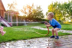 Free Cute Adorable Caucasian Blond Toddler Boy Enjoy Having Fun Watering Garden Flower And Lawn With Hosepipe Sprinkler At Stock Images - 189510544