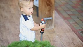 Cute adorable caucasian blond toddler boy having fun helping parents watering garden and lawn with hose and sprinkler at. House backyard stock video footage