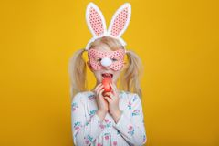 Caucasian blonde girl in white dress with pink Easter bunny ears royalty free stock image
