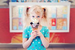 Caucasian blonde preschool girl child with blue eyes holding ice cream in large waffle cone. Cute adorable Caucasian blonde preschool girl child with blue eyes royalty free stock image