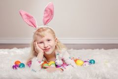 Girl with bunny ears and toys eggs celebrating Easter holiday Stock Photography