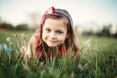 Free Cute Adorable Caucasian Girl Among Dandelions Flowers. Child Lying In Grass On Meadow. Outdoors Fun Summer Seasonal Children Royalty Free Stock Image - 186434556