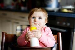 Cute adorable ewborn baby girl holding nursing bottle and drinking formula milk. Cute adorable baby girl holding nursing bottle and drinking formula milk. First stock image