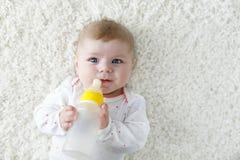 Cute adorable ewborn baby girl holding nursing bottle and drinking formula milk Stock Photography