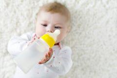 Cute adorable ewborn baby girl holding nursing bottle and drinking formula milk Royalty Free Stock Photo