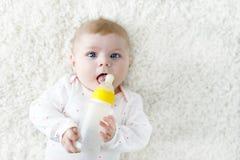 Cute adorable ewborn baby girl holding nursing bottle and drinking formula milk Stock Images