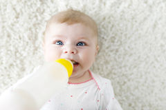 Cute adorable ewborn baby girl holding nursing bottle and drinking formula milk Royalty Free Stock Images