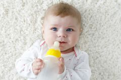 Cute adorable ewborn baby girl holding nursing bottle and drinking formula milk. First food for babies. New born child. Little girl laying on white background royalty free stock images