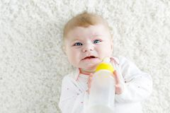 Cute adorable ewborn baby girl holding nursing bottle and drinking formula milk. First food for babies. New born child, little girl laying on white background royalty free stock images