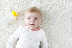 Cute adorable ewborn baby girl holding nursing bottle and drinking formula milk. New born child, little girl laying on. White background. Family, new life stock photo