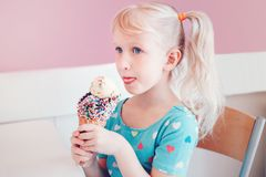 Caucasian blonde preschool girl child with blue eyes holding ice cream in large waffle cone stock images