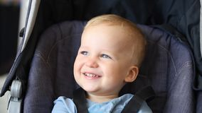 Cute adorable happy caucasian blond toddler boy sitting in stroller and laughing playing seek and hide game. Funny