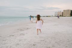 Cute Adorable Happy Young Little Girls in Pretty Dresses Playing On Vacation at the Tropical Beach by the Water on Destination Vac stock images