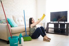 Cheerful woman clicking selfie. Cute and adorable house maid clicking a selfie after finishing house chores in living room Stock Photo