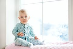 Cute adorable little baby girl sitting by window and looking to cam. Kid enjoy snowfall. Happy holidays and Christmas! Winter Home. Family Child People Royalty Free Stock Image