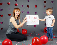 Cute adorable little white Caucasian blond boy toddler with mother in studio with red hearts and balloons on grey background Stock Photo