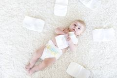 Cute adorable newborn baby of 3 moths with diapers. Hapy tiny little girl or boy looking at the camera. Dry and healthy stock image
