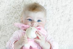 Cute baby girl playing with colorful pastel vintage rattle toy. Cute adorable newborn baby playing with colorful pastel plush bunny toy. New born child, little royalty free stock photography