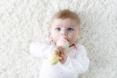 Cute baby girl playing with colorful pastel vintage rattle toy. Cute adorable newborn baby playing with colorful pastel vintage rattle toy. New born child royalty free stock photo