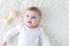 Cute adorable newborn baby playing with colorful pastel vintage rattle toy. New born child, little girl looking at the. Camera. Family, new life, childhood royalty free stock photos
