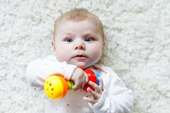 Cute adorable newborn baby playing with colorful rattle toy on white background. New born child, little girl looking at. The camera. Family, new life, childhood royalty free stock photos