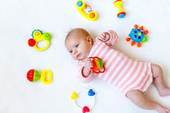 Cute adorable newborn baby playing with colorful rattle toy. in white bed at home. New born child, little girl looking. Cute adorable newborn baby playing with stock photo
