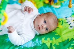 Cute adorable newborn baby playing on colorful toy gym Royalty Free Stock Photography