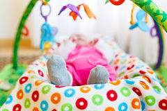Cute adorable newborn baby playing on colorful toy gym Stock Images