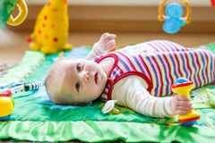 Cute adorable newborn baby playing on colorful toy gym Royalty Free Stock Photos