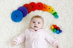 Cute baby girl playing with colorful wooden rattle toy. Cute adorable newborn baby playing with colorful wooden rattle toy ball on white background. New born Royalty Free Stock Images