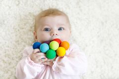 Cute baby girl playing with colorful wooden rattle toy. Cute adorable newborn baby playing with colorful wooden rattle toy ball on white background. New born royalty free stock photography