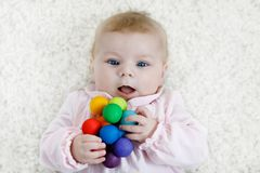 Cute baby girl playing with colorful wooden rattle toy. Cute adorable newborn baby playing with colorful wooden rattle toy ball on white background. New born stock images