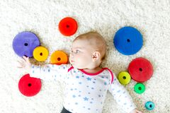 Cute baby girl playing with colorful wooden rattle toy. Cute adorable newborn baby playing with colorful wooden rattle toy ball on white background. New born stock photography