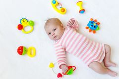 Cute adorable newborn baby playing with lots of colorful rattle toys on white background. New born child, little girl stock photography