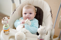Cute adorable newborn baby sitting in swing Stock Photos