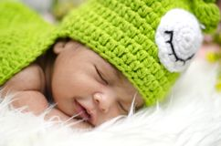 Cute adorable newborn baby sleeping on furry mat.motherhood and parenting concept. Close-up shot,cute adorable newborn baby smile and sleep on furry mat royalty free stock photography