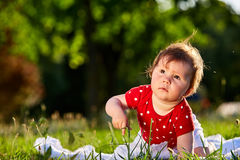 Cute adorable nice baby girl in red spring dress smiling sitting under the tree Stock Photo