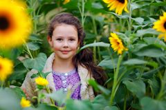 Cute adorable school girl on sunflower field with yellow flowers. Beautiful preschool child with blond hairs. Happy. Healthy little daughter, smiling and royalty free stock images