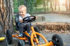 Free Cute Adorable Smiling Caucasian Toddler Boy Sitting At Pedal Toy Car And Hold, Steering Wheel By Hands Driving It Outdoors In City Royalty Free Stock Image - 183617746