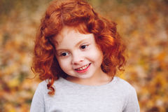 Cute adorable smiling little red-haired Caucasian girl child standing in autumn fall park outside, looking away Royalty Free Stock Images