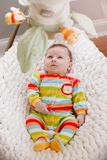Cute adorable smiling white Caucasian baby boy girl lying in bouncer chair. royalty free stock image