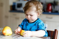 Cute adorable toddler girl eating fresh pear . Hungry happy baby child of one year holding fruit. Girl in domestic kitchen, having healthy meal snack. Smiling Stock Photography