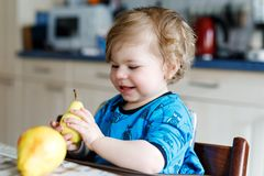 Cute adorable toddler girl eating fresh pear . Hungry happy baby child of one year holding fruit. Girl in domestic kitchen, having healthy meal snack. Smiling Royalty Free Stock Photos
